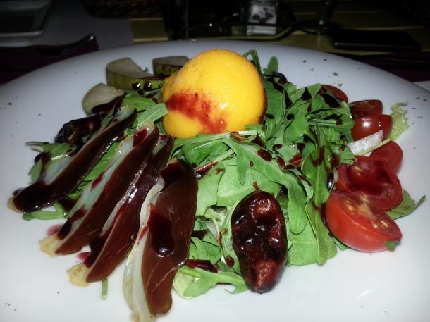 Ensalada Passionata con rúcula, jamón de pato, sorbete se mango, pera, y dátiles rellenos de queso azul
