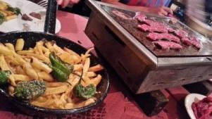 Patatas y pimientos y carne en la piedra